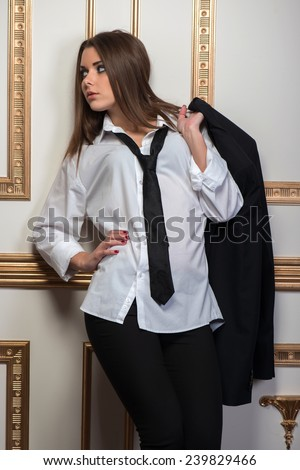 Closeup portrait of young sexy woman wearing men shirt oversize and tie leaning on the wall and holding hand behind head, provocative look, interior shot - stock photo