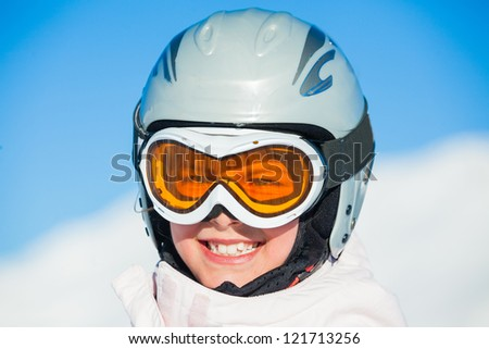Closeup portrait of young smiling girl in helmet and ski googles at winter outdoor in the Zillertal Arena, Austria - stock photo