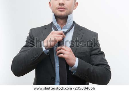 Closeup portrait of young smiling handsome businessman in suit putting on necktie isolated on white - stock photo