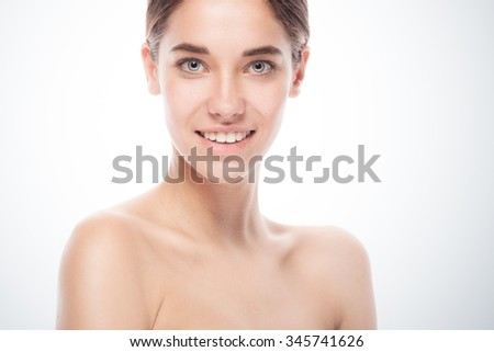 closeup portrait of young smiling woman with clean fresh skin isolated on blue gradient background - stock photo