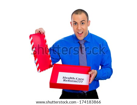 Closeup portrait of young super excited happy man holding gift with health care reform sign inside, isolated on white background. Universal health care coverage, politics, government, legislation - stock photo