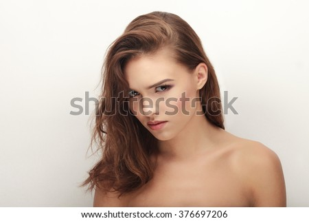 Closeup portrait of young tricky brunette woman with adorable makeup looking into camera posing on white studio background