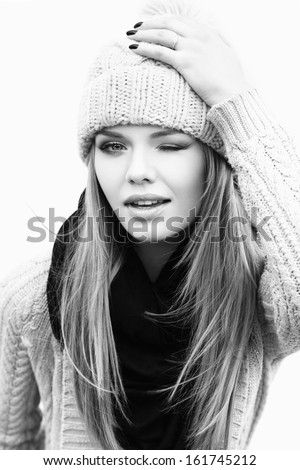 Closeup portrait of young winking girl in knit clothes, outdoors. Urban city style - stock photo