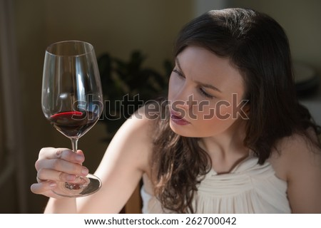 Closeup portrait of young woman drinking red wine at home - stock photo