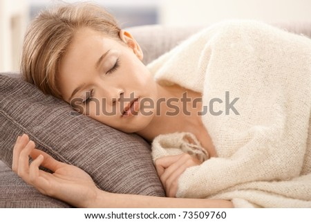 Closeup portrait of young woman sleeping on sofa at home, covered with blanket. - stock photo
