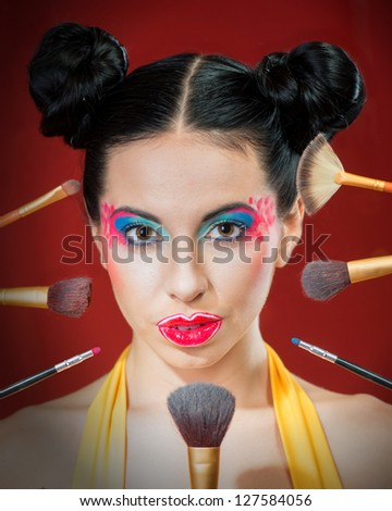 Closeup portrait of young woman with colorful makeup and cosmetic brushes