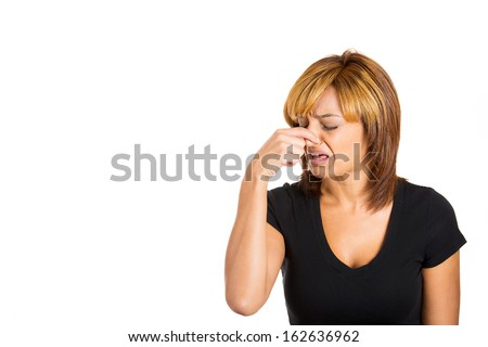 Closeup portrait of young woman with disgust on her face who covers pinches her nose looks away, something stinks, very bad smell, situation, isolated on white background. Human emotion, expression. - stock photo