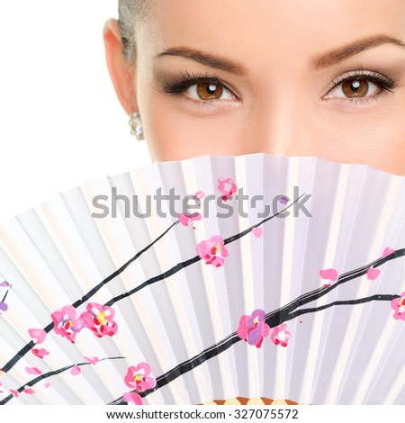 Closeup portrait of young woman with folding fan. Mixed race Asian / Caucasian female is with brown eyes. She is isolated over white background. - stock photo