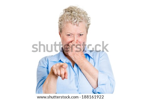 Closeup portrait old lady, senior executive, grandmother, disgust on face, pinching nose something stinks, pointing at you, displeased with situation, isolated white background. Interpersonal conflict - stock photo