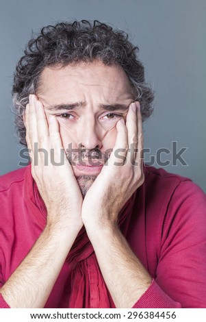 closeup portrait on sad 40's salt and pepper hair man with red sweater and scarf looking depressed and tired with both hands and face, studio shot - stock photo