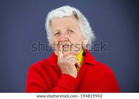 Closeup portrait pensive senior mature woman daydreaming, serious thoughts, chin on hand, wondering about stressful issues, isolated blue background. Negative emotions, facial expressions, feelings - stock photo