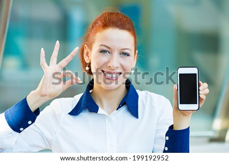 Closeup portrait, photo attractive, happy, smiling young business woman presenting, holding smartphone, screen, giving ok sign isolated background corporate office windows. Positive face expression - stock photo