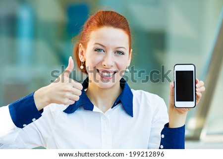 Closeup portrait, photo attractive, happy, smiling young business woman presenting, holding smartphone, screen, giving thumbs up isolated background corporate office windows. Positive face expression - stock photo