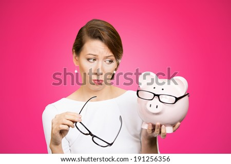 Closeup portrait poor stressed, upset, sad unhappy young woman looking at piggy bank, thinking, isolated pink background. Financial difficulties bad economy debt concept. Negative emotion, expression - stock photo