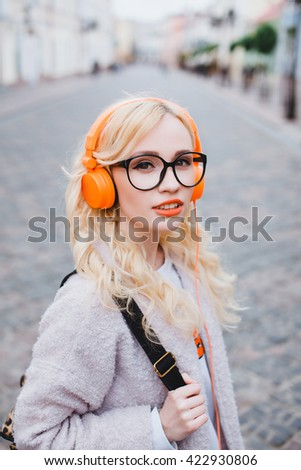 closeup portrait pretty young girl, blonde in a bright orange colored glasses, a pink sweater with backpack posing outdoors and listening to music on the player with headphones, street style - stock photo