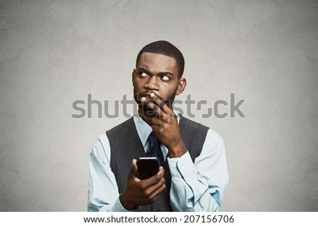 Closeup portrait puzzled confused business man looking up thinking what to reply to received text message on cell phone, texting isolated black background. Human face expression reaction body language - stock photo