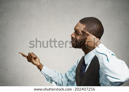 Closeup portrait rude, difficult, angry young man gesturing with fingers against his temple, are you crazy? Isolated black, grey background. Negative human emotion, facial expression, feeling reaction - stock photo