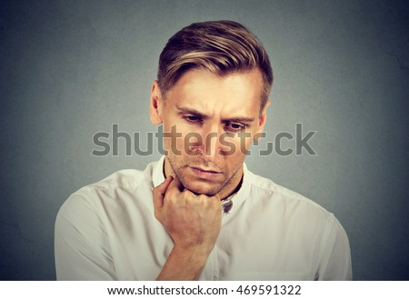 Closeup portrait sad young handsome man with worried stressed face expression looking down