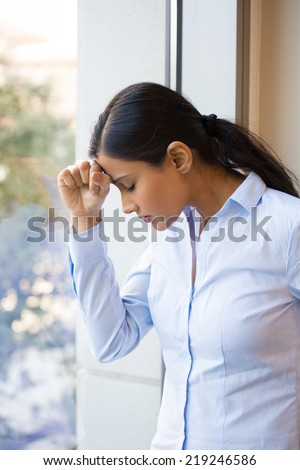 Closeup portrait, sad young woman in blue shirt, head on hand on window, really depressed, down about something, isolated city background. Negative emotion facial expression feeling body language