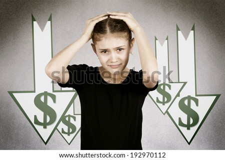 Closeup portrait scared, funny looking little girl, hands on head, stressed, market, dollar going down, isolated dark, grey background with arrows. Facial expressions, emotions. Future economy worries - stock photo