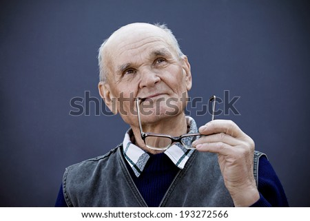 Closeup portrait senior, elderly  man with thoughtful expression, holding glasses in hands, looking up, serious, thinking, daydreaming, isolated background. Human emotions, feelings, life perception - stock photo