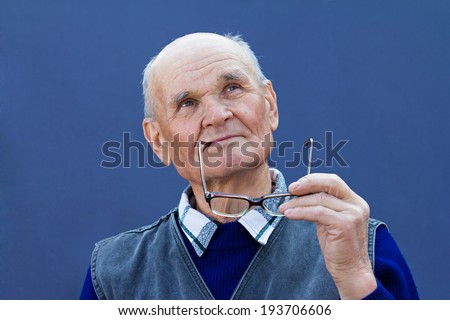Closeup portrait senior, elderly man with thoughtful expression, holding glasses in hands, looking up, serious, thinking, daydreaming, isolated blue background. Human emotions, feeling life perception - stock photo