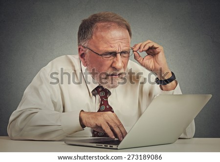Closeup portrait senior elderly mature business man with glasses having eyesight problems confused with laptop software isolated gray background. Age related changes. technology and senior people  - stock photo