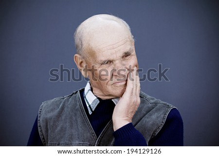 Closeup portrait senior, elderly, mature, depressed man sad, deep in thought, thinking, realizing truth, looking down isolated blue background. Human face expressions, emotions, feeling, reaction - stock photo