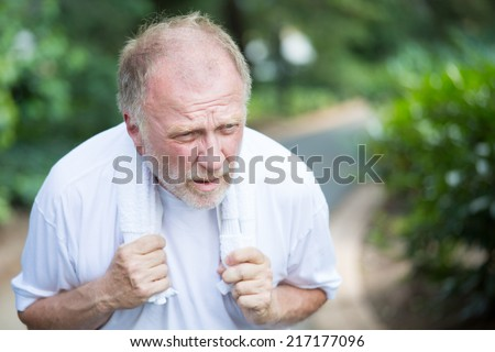 Closeup portrait, senior guy holding towel, very tired, exhausted from over exertion, sun stroke, isolated outdoors outside green trees background - stock photo