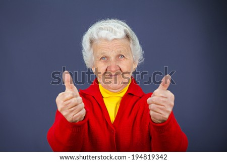 Closeup portrait senior, mature, happy, smiling excited natural woman giving thumbs up sign with fingers, isolated blue background. Positive emotions, facial expressions, symbols, feelings, attitude - stock photo