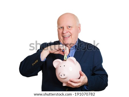 Closeup portrait, senior mature, happy, successful elderly man holding piggy bank making money cash deposit, contribution isolated white background. Clever financial decision, saving, tax free account