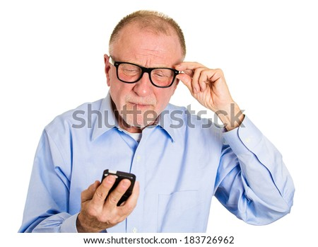 Closeup portrait, senior mature man, nerd black glasses, having trouble seeing cell phone screen because of vision problems. Bad text message. Negative human emotion facial expression feelings. - stock photo