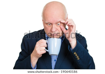Closeup portrait senior mature, tired, falling asleep business man holding cup, struggling not to crash, stay awake, keep eyes opened, isolated white background. Human emotions, facial expressions - stock photo