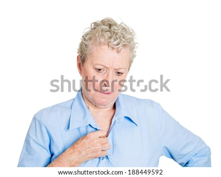 Closeup portrait, senior mature woman in deep, serious thought, nervously unbuttoning shirt, daydreaming, looking down, isolated white background. Negative human emotion facial expression feelings. - stock photo