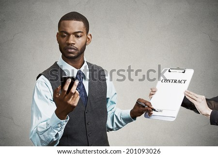 Closeup portrait serious businessman signing contract without looking at document, keeps reading news on smart phone holding mobile isolated grey background. Human face expression corporate executive  - stock photo