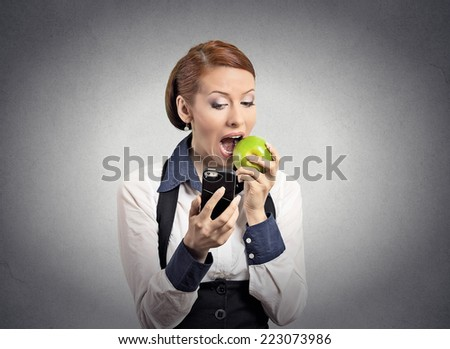 Closeup portrait serious corporate business woman, deal maker reading news on smart mobile phone holding eating green apple isolated grey wall background. Human face expression. Social media app - stock photo