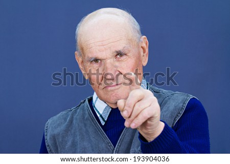 Closeup portrait serious looking, senior mature, elderly man pointing, at you with index finger, gesture, isolated blue background. Negative human emotions, facial expressions, feelings, symbols - stock photo