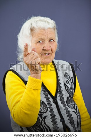 Closeup portrait serious looking, senior mature, elderly woman pointing, at you with index finger, gesture, isolated blue background. Negative human emotions, facial expressions, feelings, symbols - stock photo