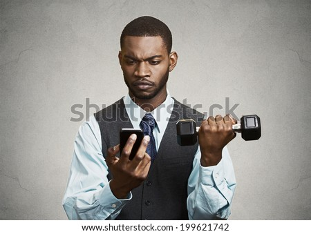 Closeup portrait serious worried business man reading bad news on smart phone holding mobile, lifting weight, dumbbell black grey background. Human face expression, emotion, corporate executive - stock photo