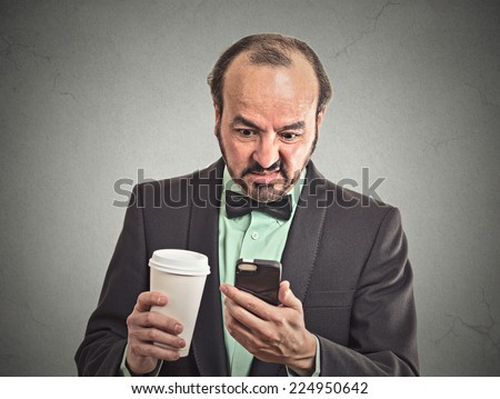 Closeup portrait serious worried business man reading bad news on smart phone holding mobile drinking cup coffee isolated grey wall office background. Human face expression corporate executive emotion - stock photo