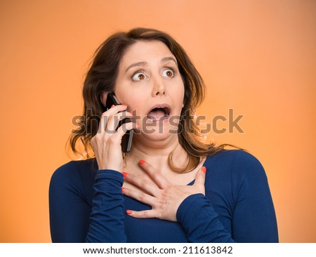 Closeup portrait shocked business woman, employee talking on cell phone having unpleasant conversation, receiving shocking news isolated orange background. Negative emotion facial expression reaction - stock photo