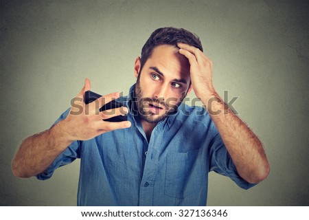 Closeup portrait, shocked man feeling head, surprised he is losing hair, receding hairline, bad news isolated on gray wall background. Negative facial expressions, emotion feeling - stock photo