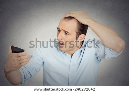 Closeup portrait shocked man feeling head, surprised he is losing hair, receding hairline or seeing bad news on cell phone isolated grey wall background. Negative facial expressions, emotion feeling - stock photo