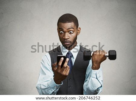 Closeup portrait shocked, surprised business man reading bad news on smart phone holding mobile, lifting weight, dumbbell isolated black background. Human face expression, emotion, corporate executive - stock photo