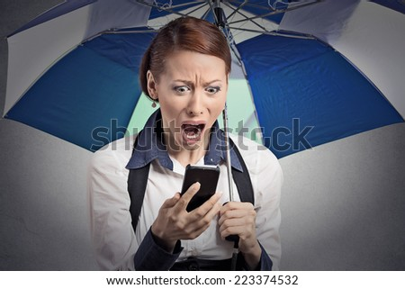 Closeup portrait shocked surprised business woman corporate executive reading bad breaking news on smart phone holding umbrella protected from rain isolated grey background. Face expression, emotion - stock photo