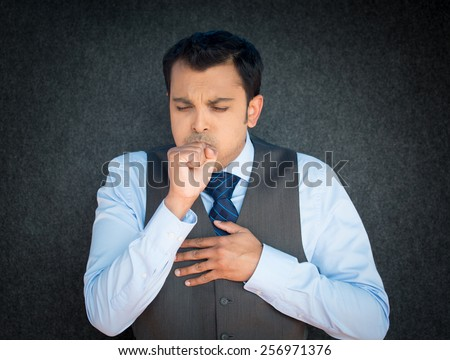 Closeup portrait, sick mature worker, executive guy in blue tie and vest, having severe infectious cough, holding chest, raising fist to mouth looking miserable unwell, isolated gray black background. - stock photo