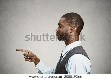 Closeup portrait side view profile young smiling handsome man pointing at you with index finger, isolated grey background. Human emotions, facial expressions, feelings, signs, symbols, body language - stock photo