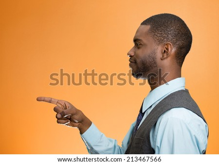 Closeup portrait side view profile young smiling handsome man pointing at you with index finger, isolated orange background. Human emotions, facial expressions, feelings, signs, symbols, body language - stock photo