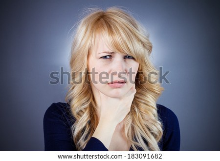 Closeup portrait skeptical, young woman looking suspicious, disgust face, mixed with disapproval, isolated dark blue background. Negative human emotion, facial expression, feeling, attitude, reaction - stock photo
