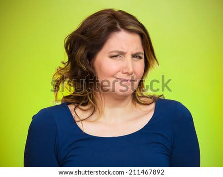 Closeup portrait skeptical young woman looking suspicious, some disgust on her face mixed with disapproval isolated green background. Negative human emotion, facial expression, feeling body language - stock photo